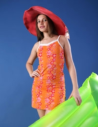 Liona in summer dress and red hat fondles ass while lying on green tube
